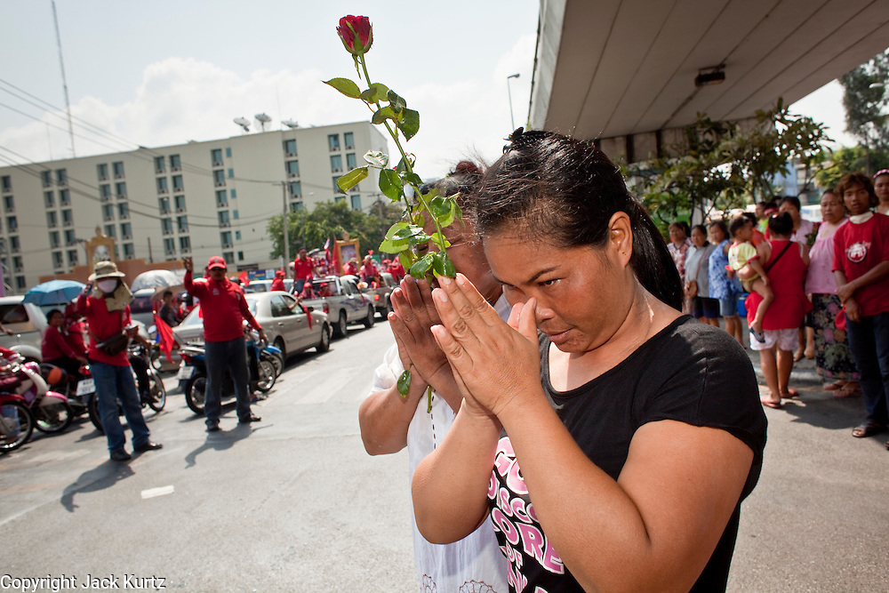 Apr. 12, 2010 - BANGKOK, THAILAND: Women present flowers to the families of Red Shirts killed in Bangkok Saturday during the funeral procession Monday. The funeral cortege for the Red Shirts killed in the violent crackdown Saturday wound through Bangkok Monday. Thousands of mourners came out to pay respects for dead Red Shirts. 21 people, including 16 Thai civilians were killed when soldiers tried to clear the Red Shirts' encampment in Bangkok. Thousands more came out to call for the government of Thai Prime Minister Abhisit Vejjajiva to step down. Today Gen. Anupong Paojinda, the Chief of Staff of the Thai Army, reiterated that the Army would not use violence to break up the protests and joined the call for the Prime Minister to call new elections. This is the beginning of Songkran, Thai New Year's week, and the government has cancelled the official festivities fearing more violence. It was during last year's Songkan festivities that the Thai Army and police used force to break up the Red Shirt protests. That protest is now called the Songkran Riots.     Photo By Jack Kurtz