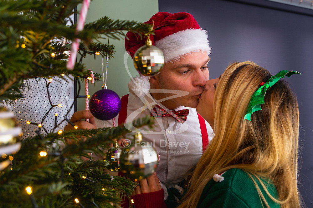 Mike and Barby steaks a kiss by the Christmas tree. Brighton, December 16 2018.
