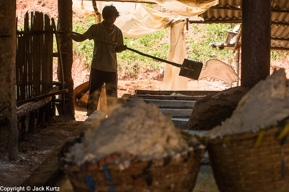 13 MARCH 2013 - BOTEN, LUANG NAMTHA, LAOS:  A worker in a salt workshop shovel water out of a pan of boiling brine in a salt workshop in Boten, Laos. Salt in Boten is made by boiling briny water and collecting the salt that is left behind. The salt wells in Boten, Laos, just south of the Chinese border, have brought a measure of fame to the area for centuries. French forces asserted French dominance over the region in 1894 to control the salt trade. Some of the salt works face an uncertain future because of economic development from China. The area is being developed into a huge parking lot to accommodate truck and tourist traffic into and out of China.   PHOTO BY JACK KURTZ