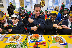 © London News Pictures. 17/12/2013 . London, UK. Deputy Prime Minister NICK CLEGG pulling Christmas crackers before eating Christmas lunch with students from St Clements Danes Primary School in London during a visit to the school. Photo credit : Ben Cawthra/LNP