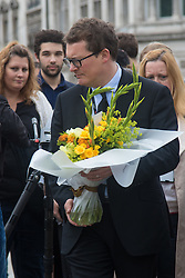 Parliament Square, Westminster, London, June 17th 2016. Following the murder of Jo Cox MP friends and members of the public lay flowers, light candles and leave notes of condolence and love in Parliament Square, opposite the House of Commons. PICTURED: A man arrives in Parliament Square with a large bouquet of flowers to leave alongside the many others.