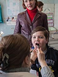 Natalya Belozorova, 38, has brought her son Maksim, 12 to see paediatrician Dr Marina Shcherbakova at an MSF mobile clinic being held at the Bolshaya Vergunka polyclinic in Lugansk.