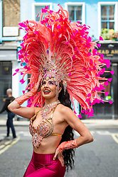 © Licensed to London News Pictures. 29/08/2021. LONDON, UK.  Samba dancers in colourful costumes take part in a flashmob around the West End organised by fashion brand RioPump GymWear.  The August Bank Holiday weekend would normally see tens of thousands of people watching events at the Notting Hill Carnival, including samba dancers, but for the second year running, the carnival has been cancelled due to Covid-19 concerns.  Photo credit: Stephen Chung/LNP