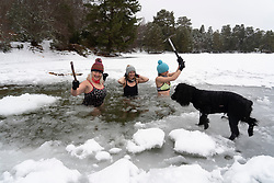 Aviemore, Scotland, UK. 4 February 2021. Loch Vaa is completely frozen and offers opportunity to walk across it. A small boathouse is now icebound and three ladies from the InVaa Dookers wild swimming group use axes to break the ice to allow them to soak in the icy water for a few minutes. Pic; Carolyn Stead, Lorna Foster and Wendy Cathcart break the ice in Loch Vaa.  Iain Masterton/Alamy Live News