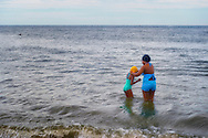 Brooklyn, New York, USA. 10th August 2013. At Coney Island beach, a mother puts a bathing cap on her daughter as they go in the Atlantic Ocean, during the 3rd Annual Coney Island History Day celebration.
