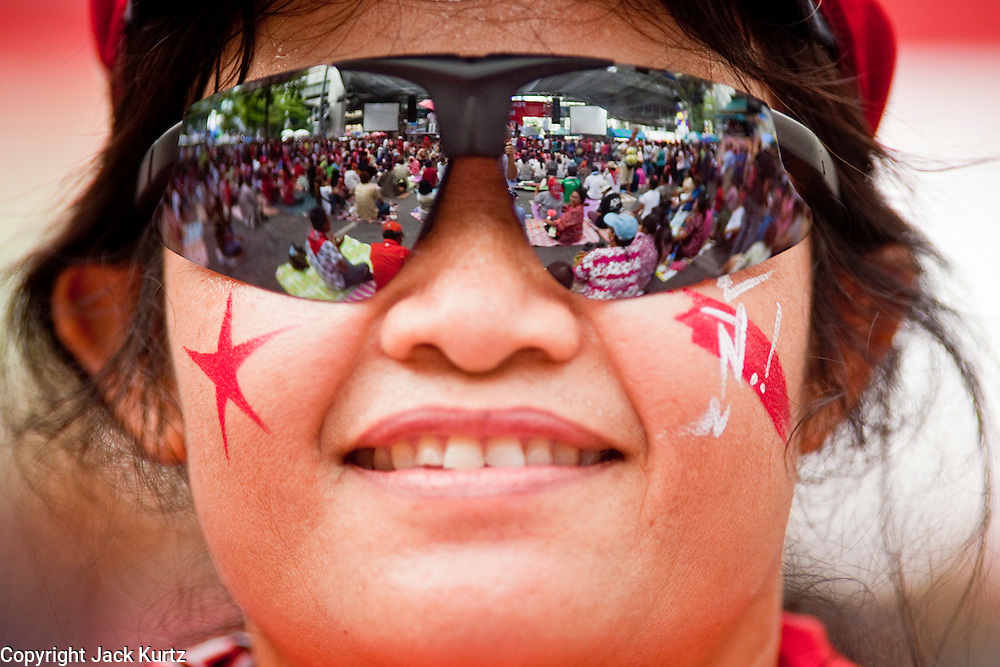 """May 12 - BANGKOK, THAILAND: The Red Shirts' main stage is reflected in a woman's sun glasses Wednesday afternoon. The Thai government said Wednesday that time has run out for """"Red Shirt"""" protesters in Ratchaprasong and Sala Daeng intersections in Bangkok and that a crackdown could come at any time. As news of the anticipated crackdown spread, Red Shirt protesters continued with an almost festive mood at their main stage but many of the sleeping areas around the protest site appeared to be empty. No official estimates on crowd size are available.  Photo by Jack Kurtz"""