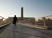 A man walks over the Millenium Bridge towards the Tate Modern art gallery in the morning in London, UK