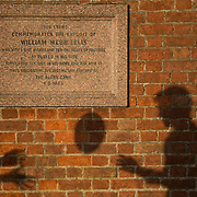 """The shadows of pupils passing a ball is cast on a plaque dedicated to William Web Ellis as they pose for another photographer at Rugby school in central England, January 20, 2015.  The public school, founded in 1567 was amongst the first """"Public"""" schools in England. The school is known as the home of rugby. Local legend  states that in 1823 pupil William Webb Ellis first ran with the ball inventing the game of rugby football which took its name from the school. In 2015 20 countries will compete in the Rugby World Cup which is hosted by England REUTERS/Neil Hall"""