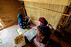 Women weaving a carpet in a  ruined, but still occupied,  kasbah near  Tazenakht, southern Morocco, Africa<br /> <br /> (c) Andrew Wilson | Edinburgh Elite media