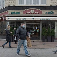People walk in front of a restaurants closed as part of the COVID-19 pandemic restrictions in Budapest, Hungary on Nov. 11, 2020. ATTILA VOLGYI