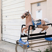 Abandoned Rocking Horse Propped up on a Table Frame Outside a Warehouse
