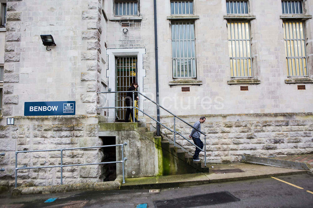A prisoner accompanied by an officer walking through the prison to visits. HMP/YOI Portland, Dorset. A resettlement prison with a capacity for 530 prisoners. Portland, Dorset, United Kingdom.