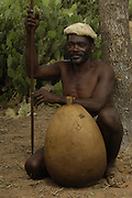 Antandroy herdsman wearing hat made from goat skin. These traditional hats are now rare to see. His shoes are hand-made from Zebu skin. The gourd is for storing water or milk and the top is closed off with a corn cob. These 'people of thorns' live in the 'spiny' forests of Southern MADAGASCAR. They are mainly Zebu (cattle) herders, their ancestors coming from mainland Africa.<br />THREATENED HABITAT<br />MADAGASCAR