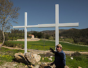 Farmer in front of crosses decoration near a church. In and around the village of Meronas.