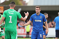 AFC Wimbledon goalkeeper Tom King (1) and AFC Wimbledon defender Ben Purrington (3) about to shake hands during the EFL Sky Bet League 1 match between AFC Wimbledon and Coventry City at the Cherry Red Records Stadium, Kingston, England on 11 August 2018.