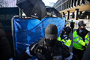 Enforcement agents employed by HS2 prevent the media from covering the removal of the last tunnel protester at Euston Station on the 26th of February 2021 in London, United Kingdom. The company erected a temporary wall and employed enforcement agents to wave umbrellas around to obscure the view trying to prevent the media from documenting the removal of the last tunnel protester, who goes under the name Bradley, who has been under ground in Euston Gardens for 31 days protesting against the HS2 high speed rail project. Bradley and several other tree protectors and climate activists have been under ground in tunnels since end of January making it one of the longest lasting tunnel protests in Britain. The garden and trees is a designated site for a temporary taxi rank in connection with the HS2 project. The HS2 high speed rail project running from London to Birmingham, Leeds and Manchester and it is estimated to cost almost £100bn.