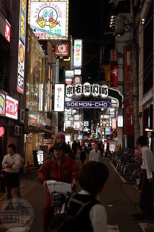 Een meisje rijdt staandend achterop de fiets van een jongen door de drukke straten van het uitgaansgebied van Osaka
