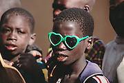 "This young boy with green heart-shaped sunglasses is reading Koranic verses on a wooden tablet under the watchful eye of the Imam of Kouakourou village in Mali as he teaches a Koranic lesson to students. Several of Soumana Natomo's children attend these classes, along with classes at what they call, ""the modern school"" taught in French, where they learn math and reading. Material World Project."