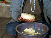 A Brokpa farmer shaping fresh cow's milk butter by hand, Thagthi village, Eastern Bhutan. Rural Bhutanese farmers make butter and cheese partly for storage or as a preserved form of milk for self consumption, with any excess being sold for cash or traded with neighbouring villages for daily necessities.