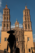 A mariachi performer is silhouetted in front of the Parroquia Nuestra Señora de Dolores Catholic Church also called the Church of our Lady of Sorrows at the Plaza Principal in Dolores Hidalgo, Guanajuato, Mexico. Miguel Hildago was a parish priest who issued the now world famous Grito - a call to arms for Mexican independence from Spain.