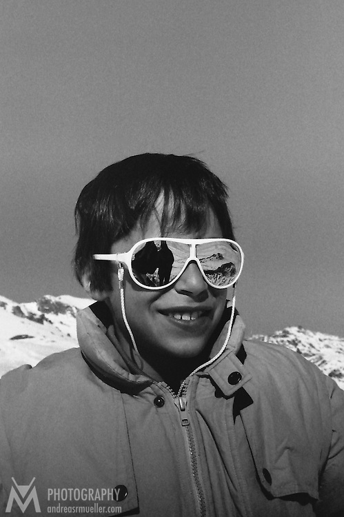 Portrait of a boy wearing reflecting sun glasses.<br />