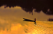 Indigenous person rowing a dugout canoe, rain forest of Ecuador, Rio Napo River.