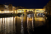 Night reflections on Ponte Vecchio in Florence Italy
