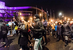 Edinburgh's Hogmanay celebrations start with the traditional torchlit procession. This year the route finishes outside the Scottish Parliament in  Holyrood where a word chosen by the young people of Scotland that makes them proud to live in the country is revealed by the thousands of torch bearers.<br /> <br /> Pictured: Revellers passing infant of the Scottish Parliament during the Torchlight Procession