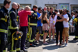 19/06/2017. London, UK. Family of fire victim Jessica Urbano embrace each other as they join firefighters at a minutes silence held near the scene of the Grenfell tower block fire. The blaze engulfed the 27-storey building killing dozens - with 34 people still in hospital, many of whom are in critical condition. Photo credit: Ben Cawthra *** Please Use Credit from Credit Field ***