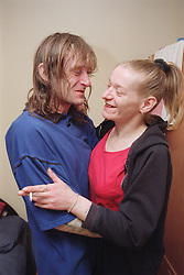 Two residents of homeless hostel embracing each other and laughing,
