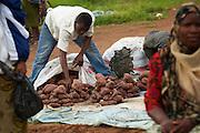 A man unloads sweet potatoes he intends to sell at Buhongwa market near Mwanza, Tanzania on Monday December 14, 2009.