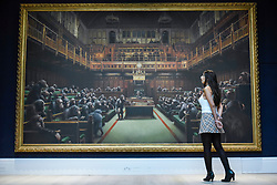"© Licensed to London News Pictures. 27/09/2019. LONDON, UK. A staff member next to ""Devolved Parliament"", 2009, by Bansky (Est. GBP1.5-2m). Preview of Sotheby's Frieze Week Contemporary Art exhibition at its New Bond Street galleries.  Over 250 works by artists, including Andy Warhol, David Hockney and Jean-Michel Basquiat, will be auctioned on 3 October 2019.  Photo credit: Stephen Chung/LNP"
