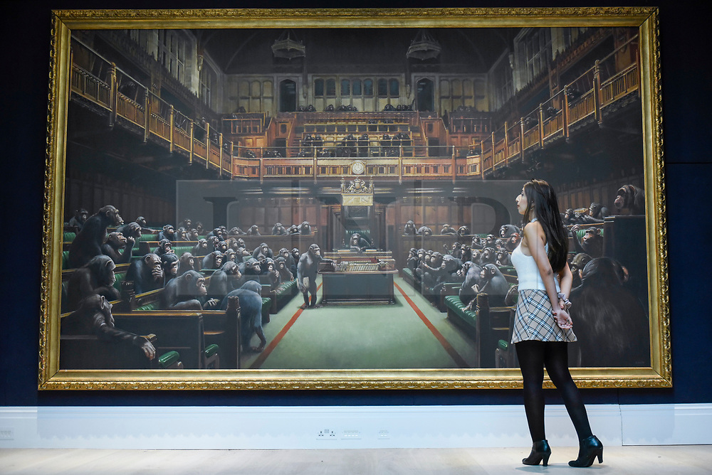 """© Licensed to London News Pictures. 27/09/2019. LONDON, UK. A staff member next to """"Devolved Parliament"""", 2009, by Bansky (Est. GBP1.5-2m). Preview of Sotheby's Frieze Week Contemporary Art exhibition at its New Bond Street galleries.  Over 250 works by artists, including Andy Warhol, David Hockney and Jean-Michel Basquiat, will be auctioned on 3 October 2019.  Photo credit: Stephen Chung/LNP"""