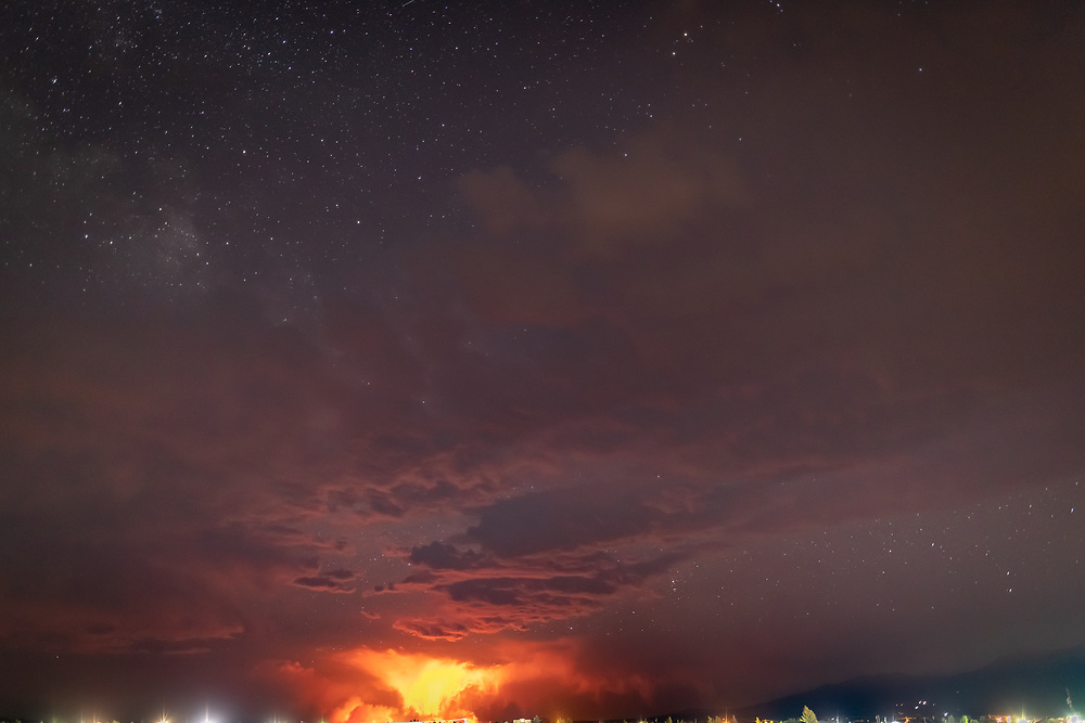 Stars and clouds rise from the orange glow of the Spring Creek fire, raging on more than 60,000 acres, some 30 miles south in Huerfano County.