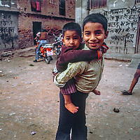 A youngster carries his brother in Kathmandu, Nepal.