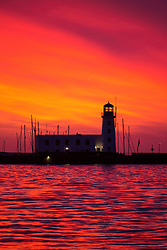 © Licensed to London News Pictures. 15/03/2017. Scarborough UK. Picture shows the red sky at dawn this morning behind the light house in Scarborough as the Met office warns of the arrival of storm Stella on Friday. Photo credit: Andrew McCaren/LNP