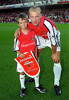 Dennis Bergkamp with the Arsenal mascot. Arsenal 2:0 Liverpool, F.A.Carling Premiership, 21/8/2000. Credit : Colorsport / Andrew Cowie.