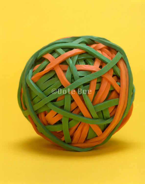 still life of rubber string ball against a yellow background
