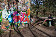 Legal graffiti in walls along The Parkland Walk, London, UK. Parkland Walk, is a 4.5 mile long strip of green land in North London that has been a nature reserve since 1990. The leafy walkway follows a disused railway which used to connect Finsbury Park and Alexandra Palace. It is also an excellent place to see graffiti in North London as many year's worth of pieces and throw ups adorn several of the bridges that the railway used to run under and abandoned buildings along the route.