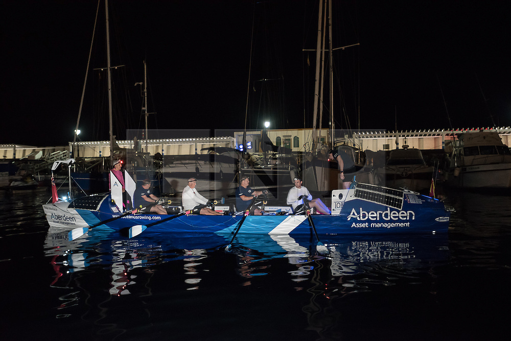 **VIDEO Available here: http://tinyurl.com/hl8y6t3 ** © London News Pictures. File pic dated 29/01/2016 Puerto de Mogan, Gran Canaria. The crew of The Toby Wallace set off to try and break the record for the fastest crossing by rowing boat of the Atlantic Ocean. MIKE JOHNSON (pictured far right sat in boat)  is currently missing at sea after their boat was rocked by a large wave causing several crew to be thrown over-board. Coastguards have now called off a search for a 21-year-old Zimbabwean rower Mike Johnson. Photo credit: credit: Ian Homer/LNP