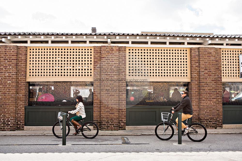 Bicyclists pass the Historic Charleston City Market on Market Street in Charleston, SC.