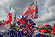 Union Jack flags and red London Routemaster buses on Westminster Bridge and the Houses of Parliament over in Westminster, on 12th September 2017, in London, England.