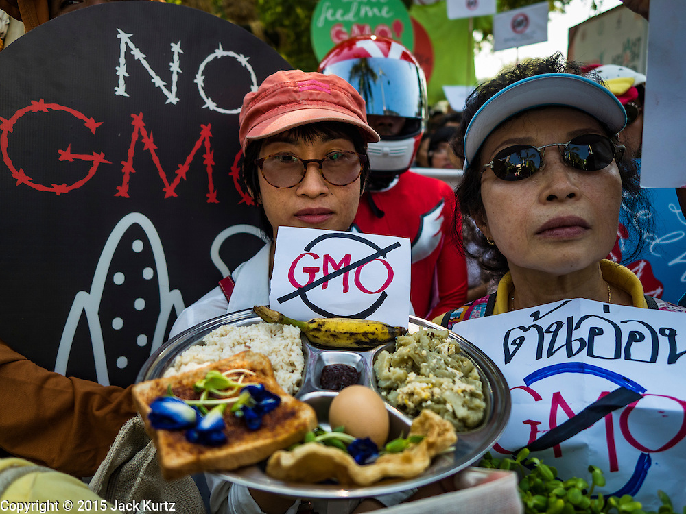 09 DECEMBER 2015 - BANGKOK, THAILAND:  People carry sample of non-GMO food during a protest against GMO foods in Bangkok. About 50 environmental activists met near Government House in Bangkok to protest against the Biological Safety Bill being debated in the Thai legislature. The bill will allow use of genetically modified organisms (GMOs) for commercial purposes. Political gatherings of more than five people are prohibited by the military government and the protestors were not allowed to march to Government House or directly confront legislators.    PHOTO BY JACK KURTZ