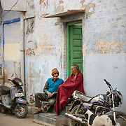 Two women in colourful saris sitting on doorstep of blue house in Jodhpur
