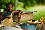 Girl roasting corn by the roadside in Dimbokro, Cote d'Ivoire on Friday June 19, 2009.