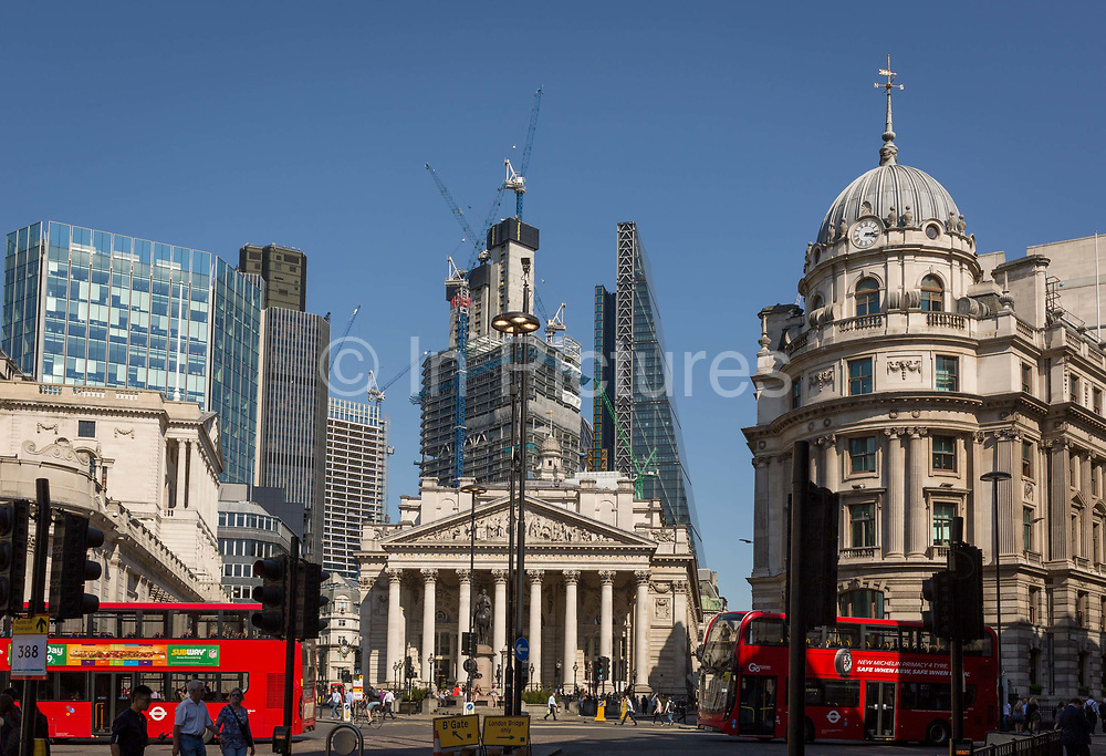 With the Bank of England on the left and neo-classical columns of Cornhill Exchange beneath new skyscrapers rising above the City of London - the capitals financial district aka The Square Mile, London buses pass through Bank Triangle with on 19th April 2018, in London, England.