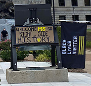 "6/28/2020 Jackson MS. <br />  Pictured outside the Mississippi State Capitol is a small group of Confederate Flag supporters and Black lives Matter advocates. The Black Lives matter advocate had a hand made sign that read "" Welcome to the Right side of History Mississippi"" .  Confederate symbol on the morning of the historic legislator vote. The Mississippi State legislators gathered at the State Capitol Sunday for a historic vote on HB1796. The MS House of Representatives  passed the Bill91-23 and the MS Senate voted 31-14 in favor of changing the flag. The Bill would allow for the redesign of the Mississippi State Flag, the current flag has the Confederate symbol on it. Mississippi is the last State in the Nation to still have the racist Confederate symbol on its state flag. Black Lives Matter advocates celebrated the historic vote outside the Capitol. The Mississippi House of Representatives passed the Bill and so did the Mississippi Senate, Governor Tate Reeves said he would sign it if it passed. Photo © Suzi Altman"
