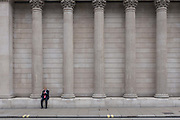 A young businessman checks messages on his phone beneath the columns of the Bank of England on Threadneedle Street in the City of London, the capitals financial district, on 3rd May 2019, in London, England.