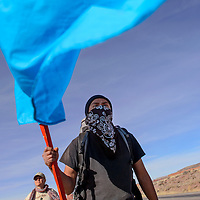 012815       Cable Hoover<br /> <br /> Tee carries a turquoise mountain flag as he and others hike one of the final legs of their journey to Mount Taylor Wednesday near Prewitt.