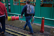 Workmen carry a spool of wiring through a Soho street in London's West End. Seen from the rear, we look at the two men manhandling the reel of electrical wires along the street from their construction site to their parked vehicle in a local car park. They walk along a side street in Chinatown in the West End of London - known for restaurants and food retail businesses.